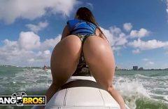 امرأة سمراء مع تجعيد الشعر الكبير مارس الجنس على طائرة على الماء