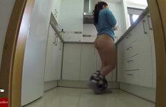 امرأة سمراء مع الملاعين الديك في المطبخ أثناء الطهي